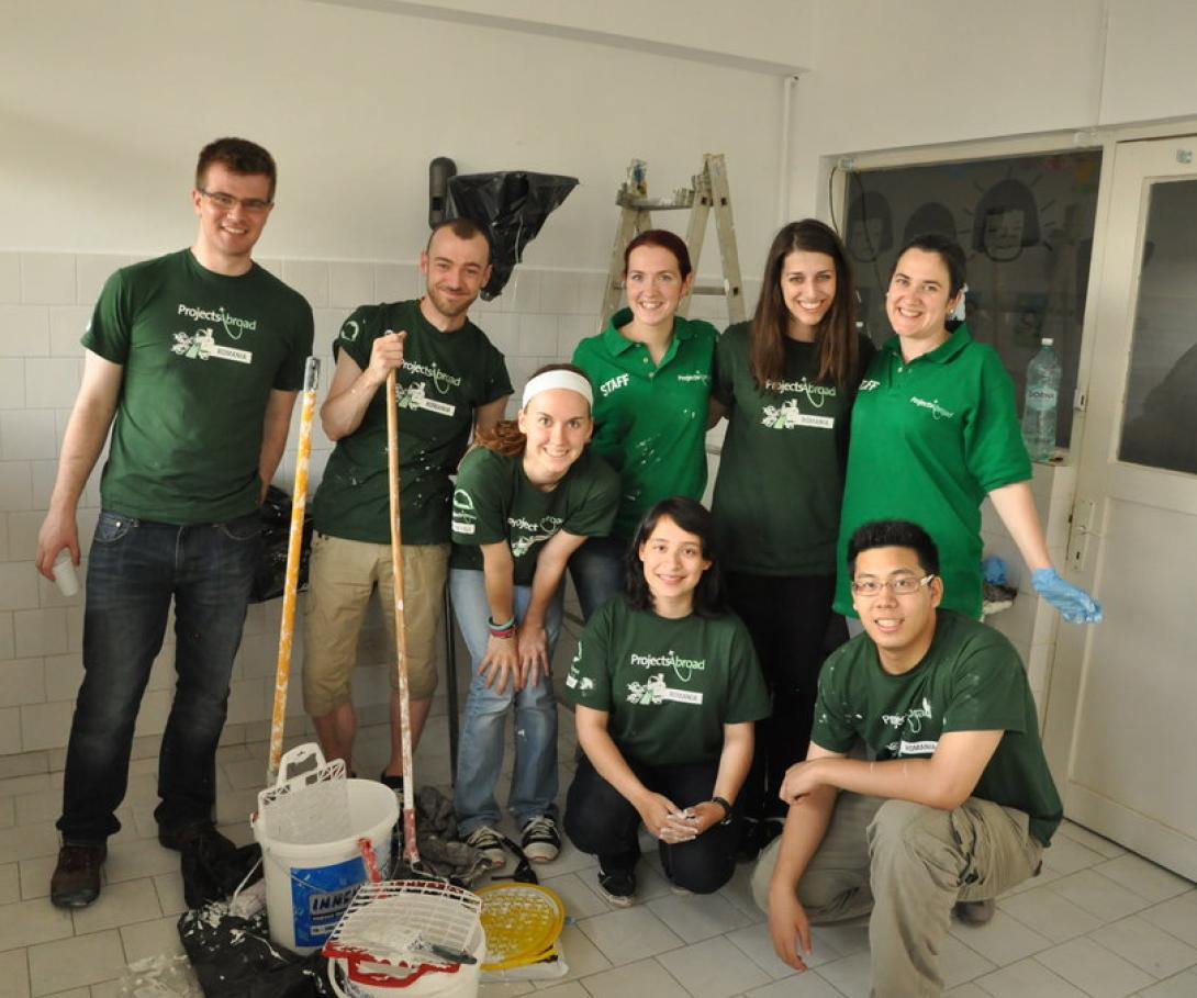 A group of volunteers in Romania, Eastern Europe give a childcare centre a new coat of paint.